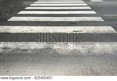 Pedestrian Crossing Of A Street With Worn And Ruined Asphalt. Zebra Crossing In A European City. Roa