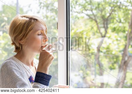 A Woman Drinking Tea At The Picture Window With Her Eyes Closed With Pleasure