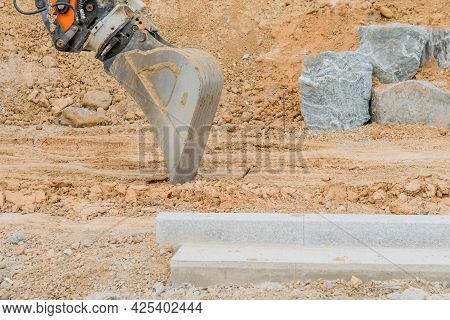 Shovel Attached To Backhoe Arm Resting On Dirt Road At Construction Site.