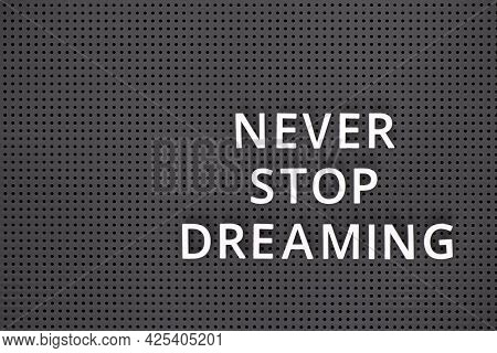 Phrase Never Stop Dreaming Spelled Out With White Letters On A Gray Pegboard