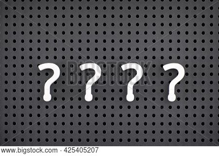 Four Question Marks Spelled Out By White Symbol On A Gray Pegboard