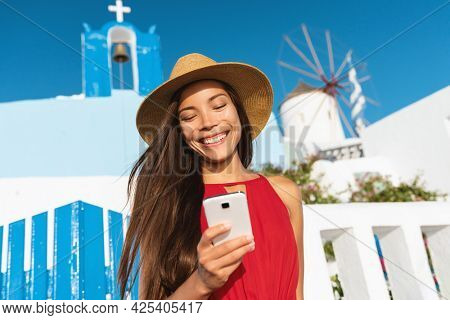 Travel vacation greece Santorini young Asian tourist woman using mobile phone texting on 5g travel data app at Oia city blue church, famous Europe destination holiday. Summer vacations.
