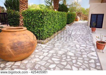 A Backyard With A Stone Footpath, Hedges, Palm Trees And A Clay Vases