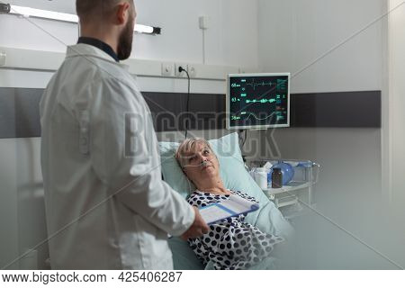 Doctor Reassuring Senior Woman Full Recovery During Discussion Consultation In Hospital Room. Writin