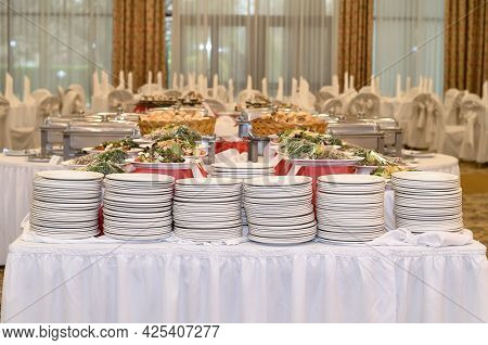Catering Table With A White Tablecloth And Six Stacks Where There Are A Lot Of White Plates And Prep