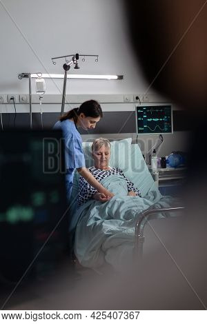 Friendly Doctor Reassuring Sick Old Patient Holding Hands, Showing Emphaty, Encouragement, During Me