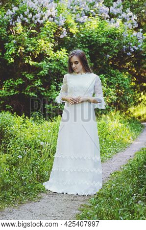 Portrait Of Young Attractive Woman In Long White Wedding Dress In Spring Garden With Blooming Trees.