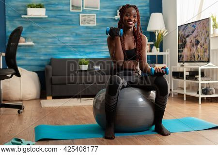 Joyful Athletic Black Person In Leggings Using Stability Ball For Training Biceps, Doing Curls With