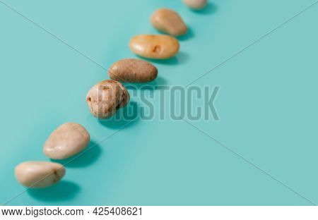 Small Brown Stones, Similar To Pebbles, Lie Diagonally On A Turquoise Background. Horizontal Picture