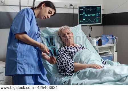 Old Patient With Lungs Illness Breathing Using Oxygen Mask Laying In Hospital Bed, Listening Nurse S