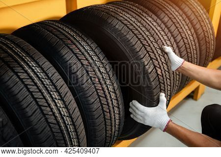 Close To The Hands Of A Tire Changer In Large Warehouse Of Car Tires, Rack With Customer Car Tires I