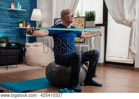 Retiree Senior Man Sitting On Swiss Ball In Living Room Doing Healthcare Fitness Exercises Streching