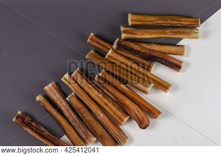 Pet Treats. A Group Of Brown Treats On A Gray And White Background. 6-inch Bully Sticks. Beef Pizzle
