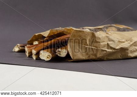 Pet Treats In A Paper Bag With Transparent Window. Dental Treats On Gray And White Background. Bully