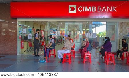 Labuan Ft,malaysia-may 17,2021:people Waiting In Of A Queue Outside Of Entrance Cimb Bank With Socia