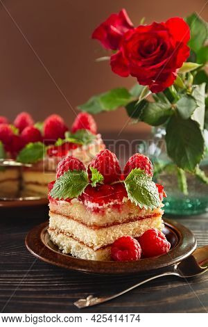 Cake. A Piece Of Beautiful Raspberry Cake On A Plate. Festive Food. Bouquet Of Red Roses In A Vase.