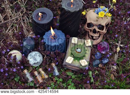 Magic Still Life With Skull, Runes, Witch Book Of Spells, Burning Candles And Potion Bottles Outside