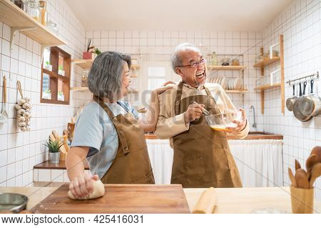 Asian Senior Couple Standing In The Kitchen At Home, Feeling Happy And Enjoy Retirement Life. Husban