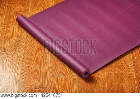 A Lilac-colored Yoga Mat Is Spread Out In A Roll On The Wooden Floor.