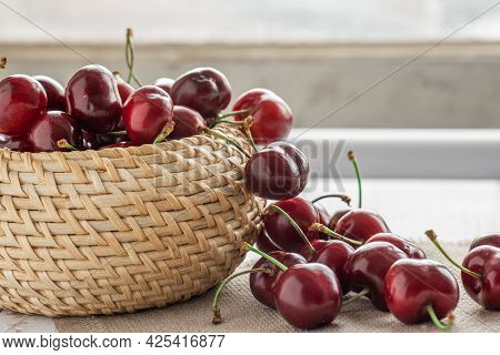 Berries Of Ripe Red Sweet Cherries In A Wicker Bowl And Poured On The Table, Cherry Harvest, Summer