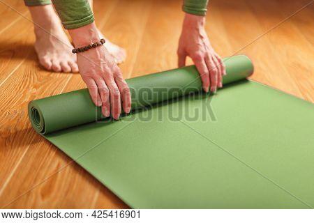 A Woman Collects A Green Mat After A Yoga Class