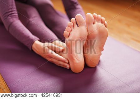 A Woman Lays Out A Lilac Yoga Mat On The Wooden Floor.