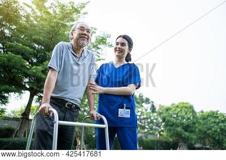 Asian Young Woman Nurse At Nursing Home Take Care Disabled Senior Elderly Man. Caregiver Doctor Serv