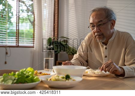 Unhappy Asian Senior Older Man Sit Alone, Eat Foods On Table In House. Depressed Mature Attractive E