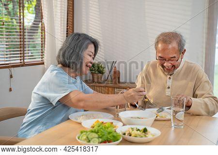 Asian Senior Olderly Couple People Eat Food On Dinner Table In House. Loving Elderly Mature Smile, E