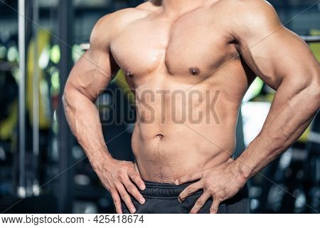 Close Up Of Bodybuilder Athlete Male Stand With Muscle In Fitness Gym. Active Shirtless Muscular Spo
