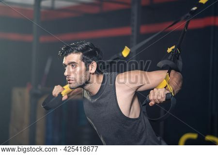 Caucasian Attractive Active Sportsmen Use Ropes Exercise In Stadium. Handsome Athlete Male Lifting U