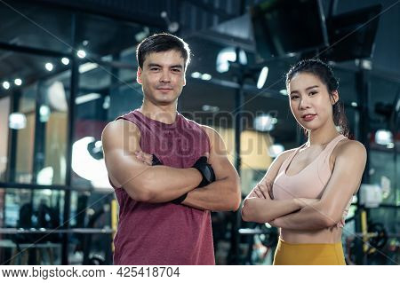 Portrait Of Active Athlete People Standing And Crossing Arms In Gym. Sportman And Woman With Six Pac