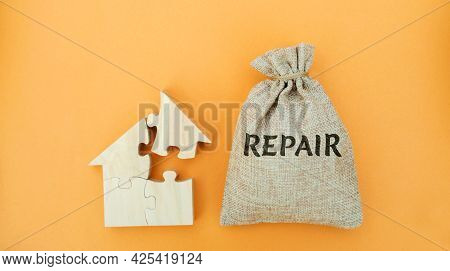 Money Bag With The Word Repair And A Wooden House. The Concept Of A Damaged House, Dilapidated Housi