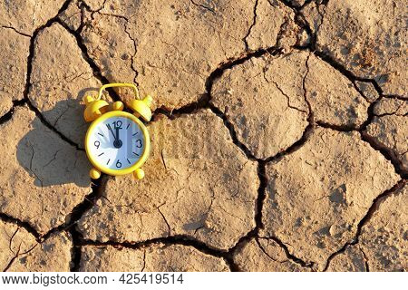 Alarm clock with five minutes before twelve o'clock on arid cracked soil. Concept of climate change or global warming.