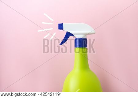 Plastic Spray Yellow Bottle With Painted Splashes Isolated On Pink Background. Bottle For Detergent