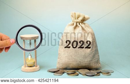 Money Bag 2022 And Hourglass. Budget Planning. Financial Goals And Plans. Business And Finance Conce