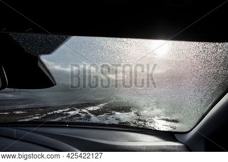 The Dewy Windscreen Of A Modern Car And A Dashboard With A Muddy Wet Road Ahead