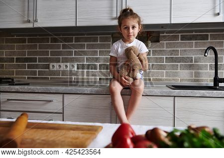 A Charming Baby Girl Is Sitting On A Kitchen Countertop With A Soft Plush Toy In Her Hands. Vegetabl