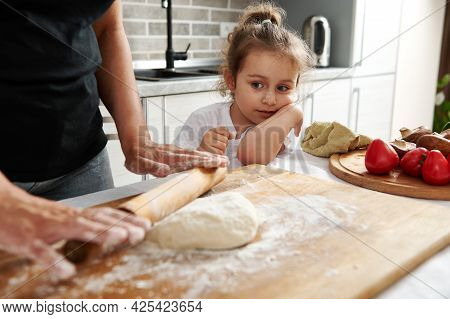 Close-up Of Cute Girl Watching Her Mother Rolling Out The Dough With A Wooden Rolling Pin. Mom And D