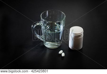Pills And Glass Of Water On Black Background