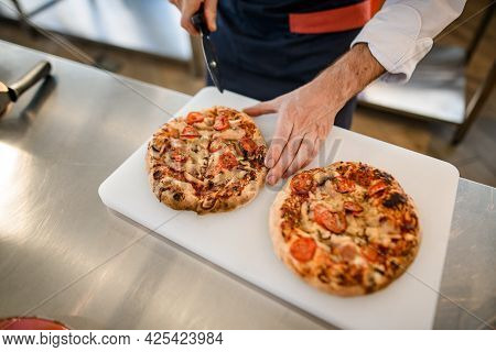 Top View On Pizzas On Cutting Board That Chef Cutted Into Pieces With Cutter