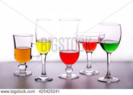 Different Types Of Crystal Glasses With Colorful Liquid Inside Isolated On White Background