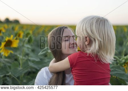 Portrait Of Happy Young Mother And Little Son On Field Of Sunflowers Background. Tenderness And Trus