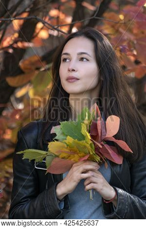 Portrait Of Brunette Girl With Autumn Leaves In Her Hands. Beautiful Young Woman In Forest. Vertical