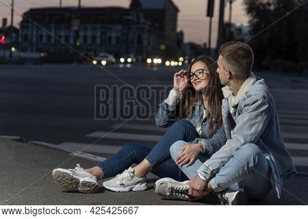 Young Couple Are Sitting On Road In The Late Evening. Young Girl And A Guy On A Date.