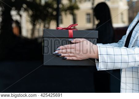 Black Gift Box With Red Bow In Female Hands. Woman Takes A Gift. Close Up, Side View