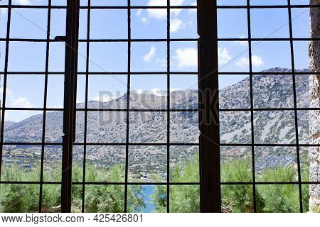 Island Spinalonga, A View Of The Beautiful World From The Barred Window Of The Prison Cell.