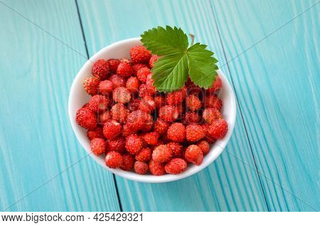 Fresh Berries Of Forest Strawberry On Light Blue Wooden Background, Top View. Strawberries In White
