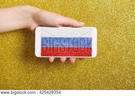 A Woman's Hand Holds A Phone With A Screensaver Of The Flag Of Russia On A Golden Background.backgro