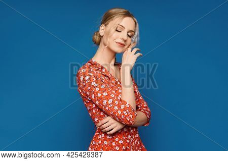 A Model Girl In A Colorful Summer Dress Posing Over Blue Background, Isolated. Young Caucasian Woman